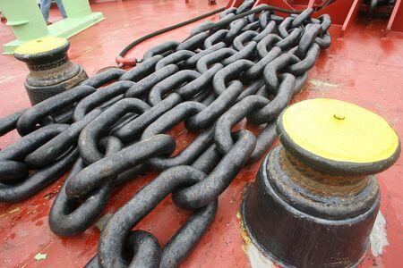 Old red marine deck with chains and bollards Standard-Bild