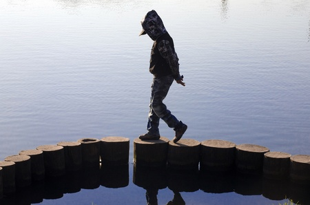 The boy in a jacket with a hood goes, having hung a head, on a construction from logs on river bank