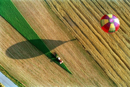 the hot air balloon soars over the earth