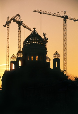 Building cranes work on building of a modern Christian cathedral in Russia. A decline Standard-Bild