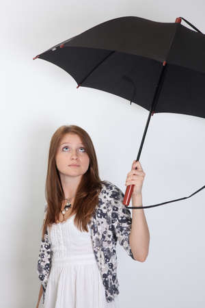 The girl holds the big umbrella and looks upwards