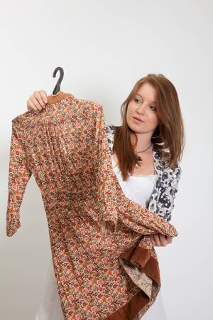 The girl considers a dress, intending it to buy