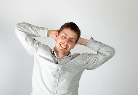 The guy in a light shirt has woken up recently. He stretches himself. A white background.