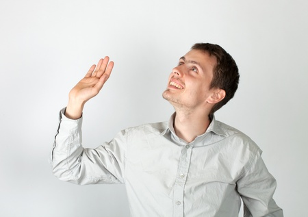 The young guy affably waves  a hand to show to someone his friendliness Standard-Bild