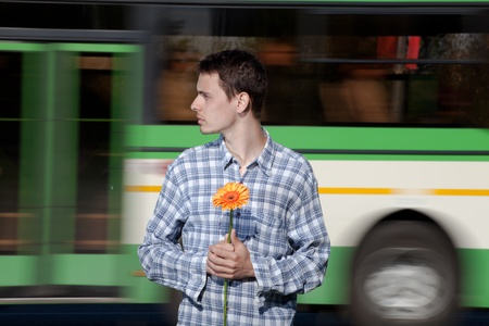 The guy with a flower in a hand waits the girl who promised to keep the appointment. He feels all emotions of the enamoured
