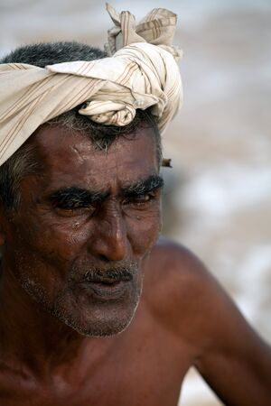 Portrait: the old man from sri lanka sits on the shore of the ocean Standard-Bild