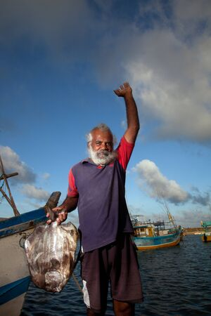 The man in the maritime market shows a big fish, rejoicing luck