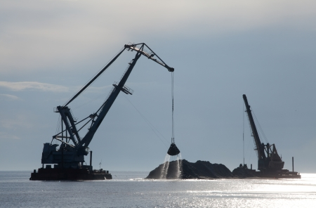 dredger: dredger pumping sand onto the coastline to gain new land from the sea Stock Photo