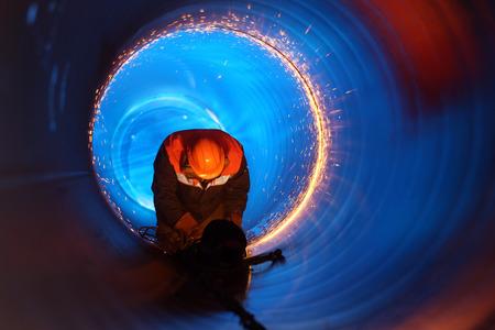 Een werknemer werkt in een pijp op een pijpleiding constructie