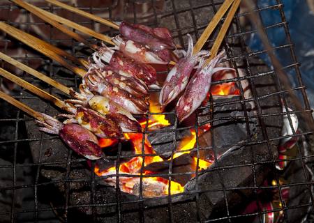 Squid cooked on a flame grill in the cafe in Cambodia Standard-Bild