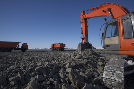 Crawler excavator loads the soil dump trucks