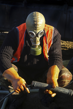 Worker in special protective clothing, masks and gloves, works in a dangerous environment