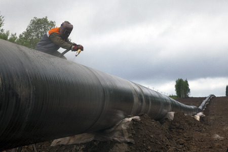 tubing: Worker using a sandblaster cleans tubing pipe before insulation Stock Photo