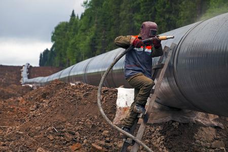 Worker using a sandblaster cleans tubing pipe before insulation Standard-Bild