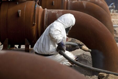 dust mask: Worker in protective equipment cleans the metal construction before painting them