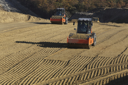 two compactors tamped sand on the pad for future construction Standard-Bild