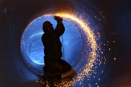 worker: Un obrero trabaja en el interior de un tubo en una construcción del gasoducto