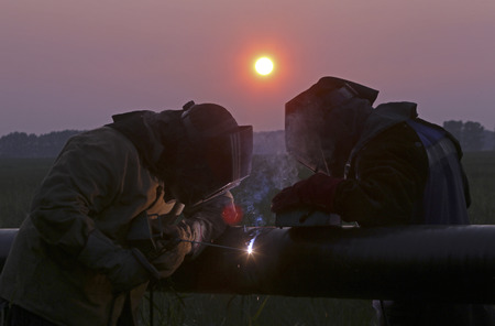 two welders working at sunset
