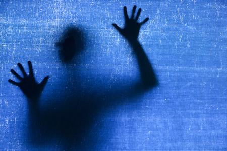 Silhouette of a man, shot through the blue fabric Standard-Bild
