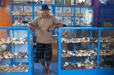 The owner a shop of Souvenirs made from sea shells on the ocean beach in Sri Lanka Standard-Bild