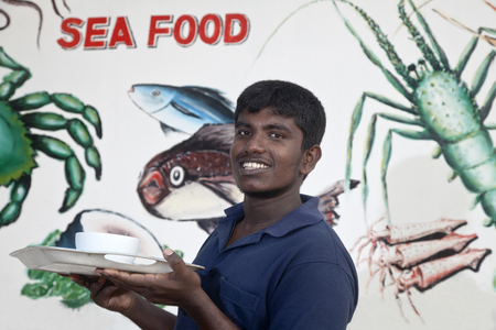 the young barman of a seafood restaurant at the Shri Lanka ocean beach keeps the dish with the ready order Stock fotó