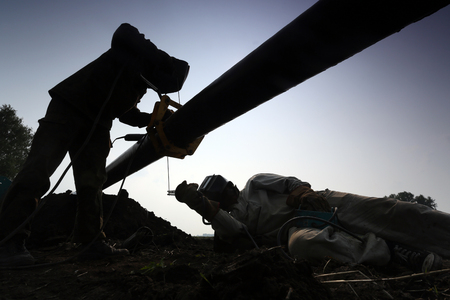 Silhouettes of two workers welding a pipe Standard-Bild