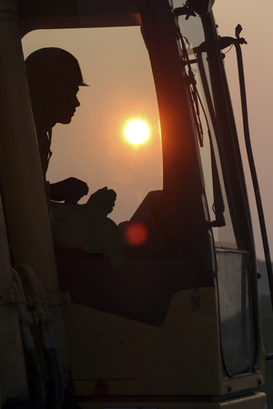 silhouette of an excavator driver in cabin on sunset Standard-Bild