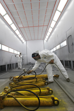 A worker paints the recovered metal parts