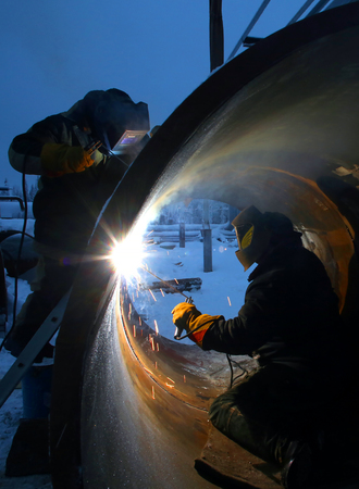 Two workers are welding inside and outside of the pipe