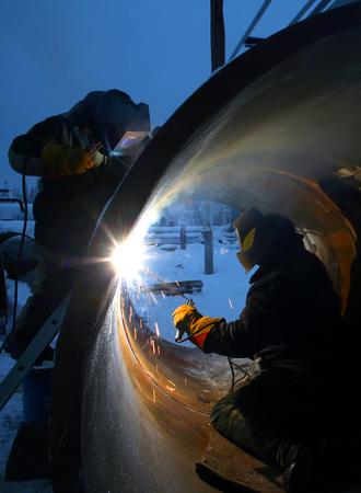 Zwei Arbeiter schweißen innerhalb und außerhalb des Rohres Standard-Bild - 76557259