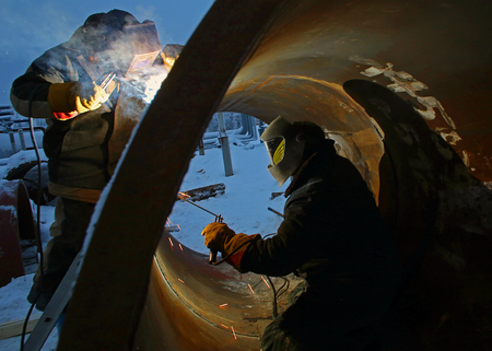 Workers are welding inside and outside of the pipe Standard-Bild