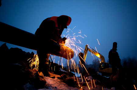 A worker grinds a pipe on the construction of a pipeline Stock fotó