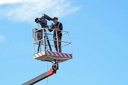 MILAN , ITALY  -10 November 2015 : Cameraman working on an aerial work platform