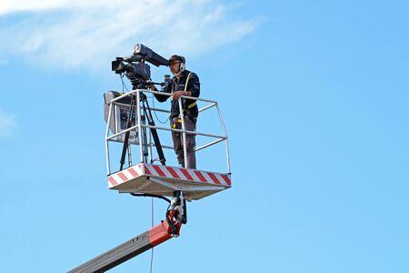 MILAN , ITALY  -10 November 2015 : Cameraman working on an aerial work platform