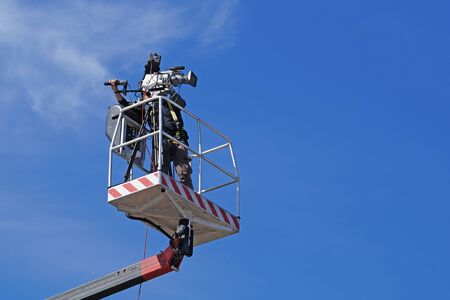 Cameraman working on an aerial work platform Stock Photo