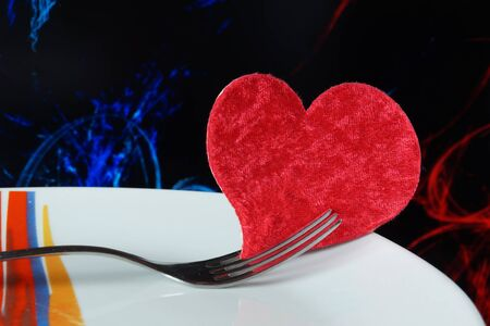 plate in shape of heart, table knife and fork on red background.