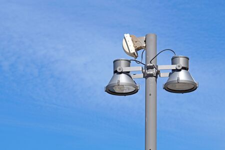 Closeup of a modern white metallic street lamppost with five lanterns against clear blue sky. Copy space.
