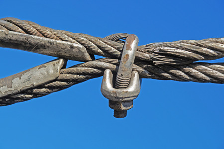 Closeup of metal fasteners and steel wire rope, metal clamp