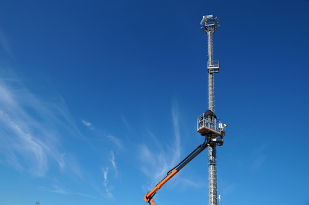 Hydraulic mobile construction platform elevated towards a blue sky with metal pole with street lamp