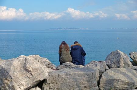 mujer mirando el horizonte: personas que se sientan en las rocas mirando el horizonte