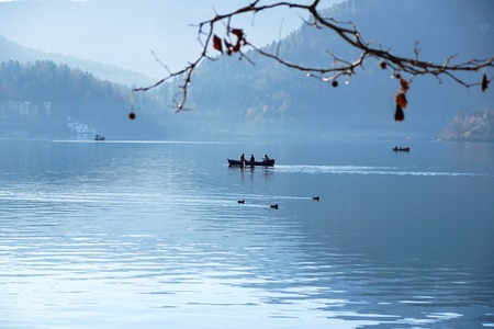 silhouette of people rowing a boat in the river at lake