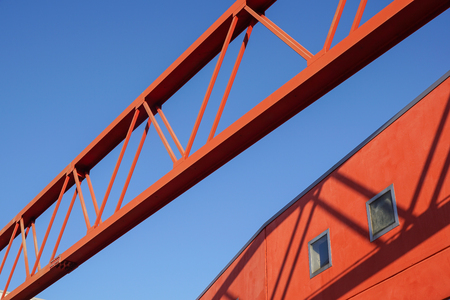 Steel beam construction pointing to the blue sky whit red facade