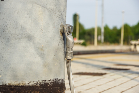 grounded: Structural detail of a lighting post steel base plate. Safety ground wire attached. Stock Photo