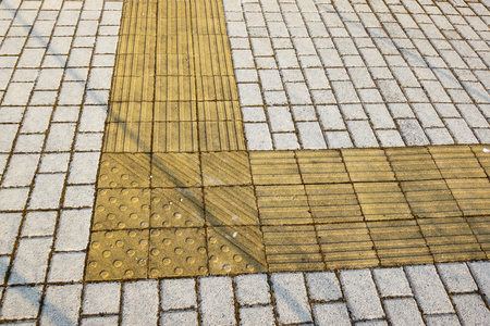 guides: Sidewalk guides for blind. Yellow concrete cobblestones on walkway for blindness people