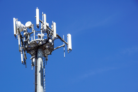Top part of cell phone communication tower with multiple antennas against a blue sky
