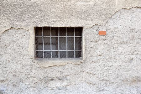 metal grate: Background colorful and weathered wall with window protected by a grid and plumbing pipes