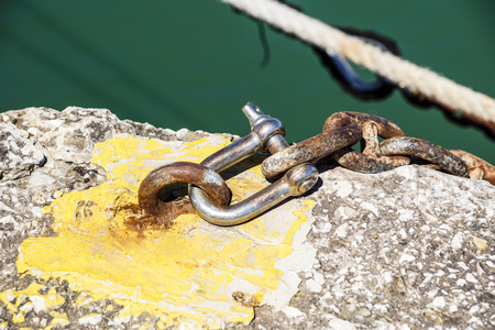 Rusty metal shackle on a metal bar laying on weathered wood outdoors