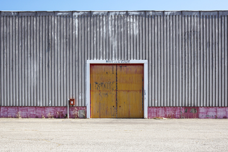 metal structure: The sheet metal factory wall with the entrance door in the industrial park.The red door of the factory building Stock Photo