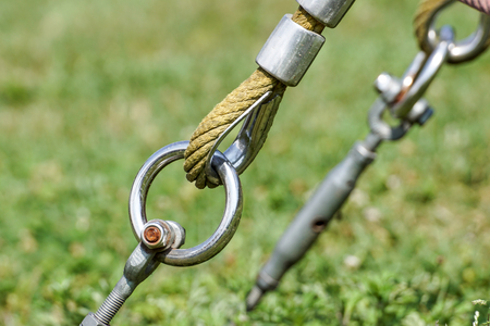 End of swinging rope hang on metal construction in a park. Rough rope end in metal circles and safety snap hook Stock Photo