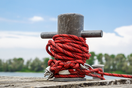 Worn old rusty mooring bollard with heavy ropes on the deck of a ship, closeup.